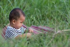 Asian child boy sit on Thai mat in the garden. Asian child boy sit on Thai mat in the garden,concept of learning and health Royalty Free Stock Image