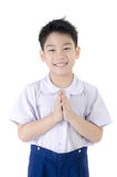 Asian child boy in student's uniform acting sawaddee on isolated Stock Photos