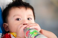 Asian child  boys eating milk from bottles. And looking Royalty Free Stock Photography
