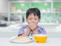 Boy close his mouth by hand between having lunch. Asian child close his mouth by hand between having lunch Stock Photos