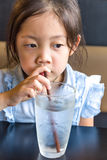 Asian Child Drinking Water from Glass. Using straw stock photo