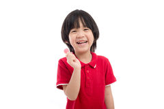 Asian child eating a lollipop on white background Royalty Free Stock Images
