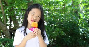 Asian Child Eating Popsicle Ice Cream in Hot Summer Day stock video