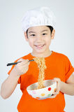 Asian child eating ramen noodles in ceramic bowl . Royalty Free Stock Photo