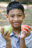 Asian Child Enjoy with Fruit. Asian child feeling happy when he got a fruit in his hand Stock Photo