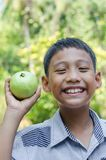 Asian Child Enjoy with Fruit. Asian child feeling happy when he got a fruit in his hand Stock Photography