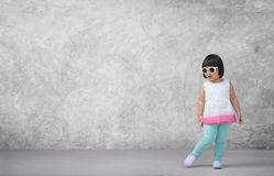 Asian child girl with concrete wall background in empty room Stock Image