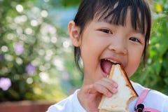 Asian child girl eating a sandwich stock photos