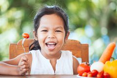 Asian child girl eating tomato and learning about vegetable. Cute asian child girl eating tomato and learning about vegetables with happiness royalty free stock image