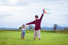 Asian child girl and father with a kite running and happy on mea. Dow in summer in nature Royalty Free Stock Images