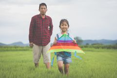 Asian child girl and father with a kite running and happy on mea Stock Photo