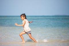 Asian child girl having fun to play and run on beach near the beautiful sea in summer vacation. Cute asian child girl having fun to play and run on beach near royalty free stock photo