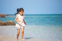 Asian child girl having fun to play and run on beach near the beautiful sea in summer vacation. Cute asian child girl having fun to play and run on beach near stock image