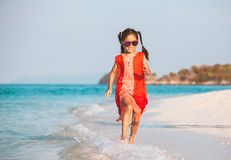 Asian child girl having fun to play and run on beach near the beautiful sea in summer vacation. Cute asian child girl having fun to play and run on beach near royalty free stock photography