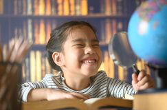 Asian child girl industrious is sitting at a desk indoors. Kid is learning in home royalty free stock images