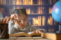 Asian child girl industrious is sitting at a desk indoors. Kid is learning in home stock photo