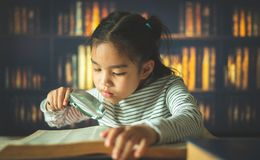 Asian child girl industrious is sitting at a desk indoors. Kid is learning in home royalty free stock photo
