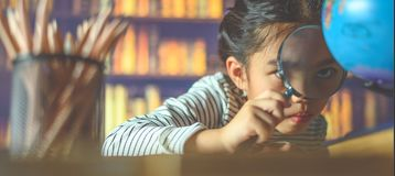 Asian child girl industrious is sitting at a desk indoors. Kid is learning in home royalty free stock photography