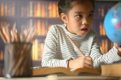 Asian child girl industrious is sitting at a desk indoors. Kid is learning in home stock image