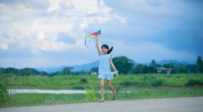 Asian child girl with a kite running and happy on meadow in summ Royalty Free Stock Photography