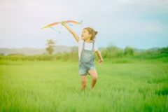 Asian child girl with a kite running and happy on meadow in summ royalty free stock images