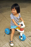 Asian child girl playing on toy with wheels Stock Images