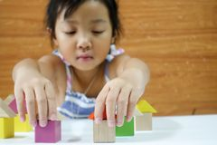 Asian child girl is playing wooden toys stock photos
