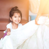 Asian child girl smiling and having fun to play with blanket Stock Image