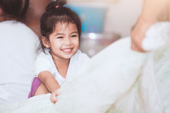 Asian child girl smiling and having fun to play with blanket Royalty Free Stock Photo