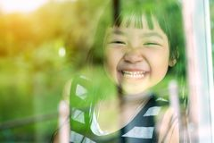 Asian child girl standing on glass mirror reflecting green forest. She was smiling in a good mood stock photo