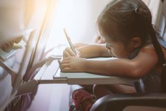 Asian child girl traveling by an airplane and spending time by drawing and reading a book during the flight. Cute asian child girl traveling by an airplane and royalty free stock photography