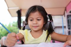 Asian child girl use Pencil write letters on the book. Asian child girl use Pencil write letters on the book in concept of education and learning Stock Photo