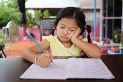 Asian child girl use Pencil write letters on the book. Asian child girl use Pencil write letters on the book in concept of education and learning Stock Images