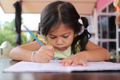 Asian child girl use Pencil write letters on the book. Asian child girl use Pencil write letters on the book in concept of education and learning Royalty Free Stock Photos