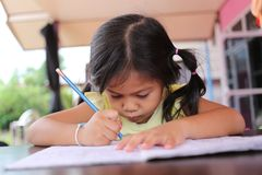 Asian child girl use Pencil write letters on the book. Asian child girl use Pencil write letters on the book in concept of education and learning Royalty Free Stock Images