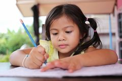Asian child girl use Pencil write letters on the book. Asian child girl use Pencil write letters on the book in concept of education and learning Royalty Free Stock Photography