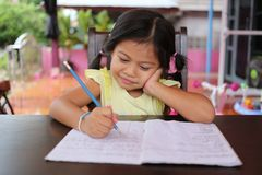 Asian child girl use Pencil write letters on the book. Asian child girl use Pencil write letters on the book in concept of education and learning Stock Photography