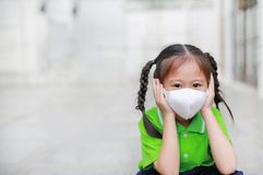 Asian child girl wearing a protection mask while outside to against PM 2.5 air pollution with pointing up in Bangkok city. Thailand stock photography