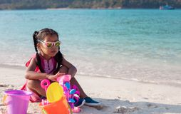 Asian child girl wearing sunglasses having fun to play with sand on beach in summer vacation. Cute asian child girl wearing sunglasses having fun to play with stock photo