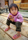 Asian child girl 4 years old, holding cookie, in countryside. Stock Photos