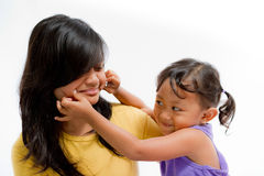 Asian Child Happy Playing Pinch Cheek with Teen Sister. Asian Little Girl Having Fun Pinch Teen Sister Cheek Royalty Free Stock Photography