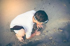 Asian child has fun digging in the sand. Young boy enjoying on b Royalty Free Stock Photos