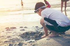 Asian child has fun digging in the sand. Young boy enjoying on b Stock Image