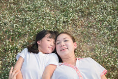 Asian child and her mother laying down Royalty Free Stock Photos