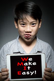 Asian child holding digital tablet ,With  WE MAKE IT EASY! Stock Photography