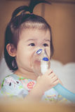 Asian child holds a mask vapor inhaler for treatment of asthma. Stock Images