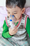 Asian child holds a mask vapor inhaler for treatment of asthma. Stock Photo