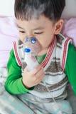 Asian child holds a mask vapor inhaler for treatment of asthma. Sad asian child holds a mask vapor inhaler for treatment of asthma on sickbed in hospital Stock Photo