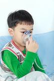 Asian child holds a mask vapor inhaler for treatment of asthma. Royalty Free Stock Photos
