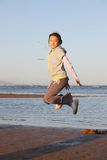Asian child jumping on beach Stock Images